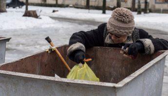 Una mujer busca comida en un contenedor de basura en Avdiivka