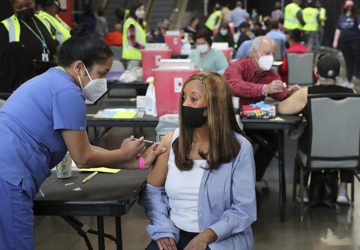 En esta foto de archivo del 23 de marzo de 2021, Anita Shetty, izquierda, vacuna a Doris Lucas en Atlanta.