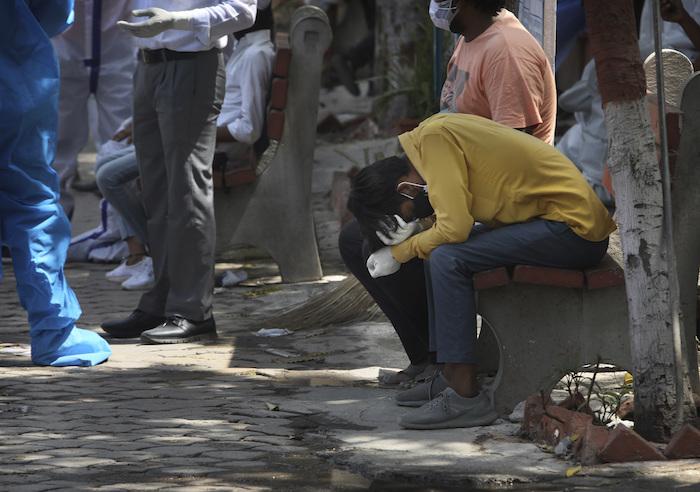Personas afuera de un crematorio para pacientes fallecidos por coronavirus, en Nueva Delhi, India, el 19 de abril de 2021.