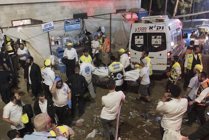 Agentes de seguridad y rescatistas israelíes cargan el cuerpo de una víctima que falleció durante las celebraciones del Lag Ba'Omer, el viernes 30 de abril de 2021 en el norte de Israel.