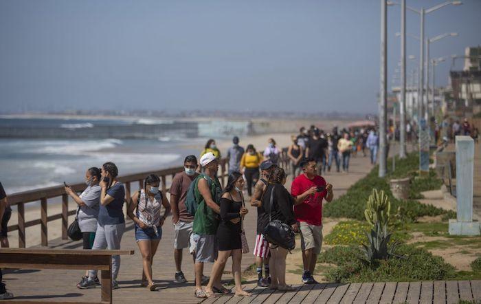 Ciudadanos pasean por el malecón de Tijuana a pesar de que la playa estaba cerrada durante la Semana Santa.