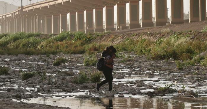 Mujer migrante cruza entre tormenta de arena el Río Bravo la frontera en Juárez.
