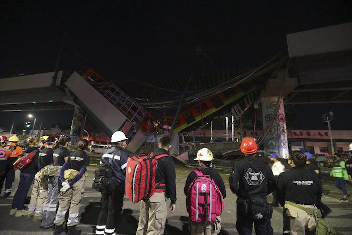 El personal de rescate se detiene frente a los vagones del Metro de Ciudad de México después de que una sección de la Línea 12 se derrumbó en la capital mexicana, el martes 4 de mayo de 2021.