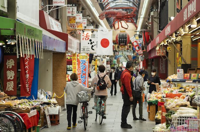 Gente con mascarillas hace las compras en el mercado Kuromon Ichiba en Osaka, Japón, martes 20 de abril de 2021.