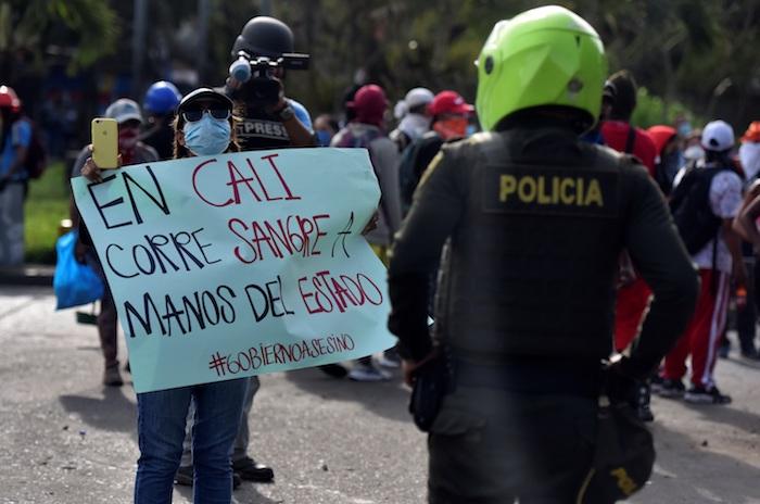 Una manifestante muestra un cartel a un policía durante unas protestas el 11 de mayo de 2021 en el barrio Siloé, en Cali (Colombia).