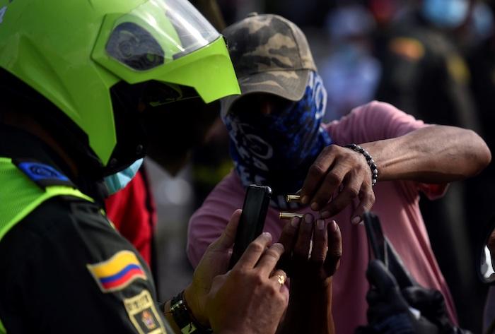 Un manifestante muestra unos cartuchos de bala a un policía durante unas protestas el 11 de mayo de 2021 en el barrio Siloé, en Cali (Colombia).