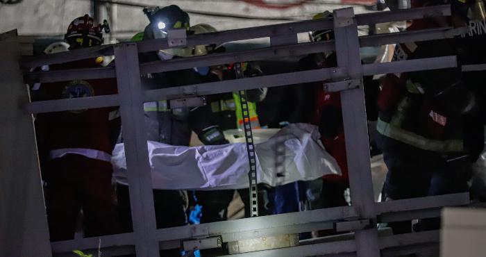 Rescatistas trasladan el cuerpo de una víctima en el sitio donde colapsó la estructura de un tramo elevado del Metro de la Línea 12 causando el desplome de los vagones de un tren, en la Ciudad de México, capital de México, el 4 de mayo de 2021.