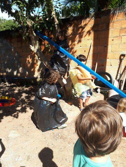 As crianças pintando a madeira da casa na árvore que estão planejando e que construirão em breve.