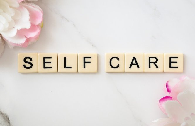 Self care written in scrabble tiles