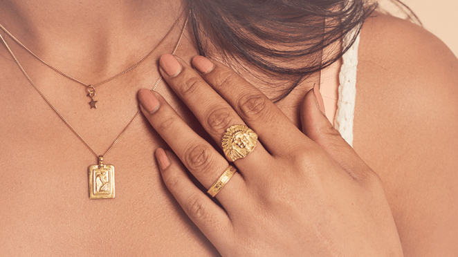 Ladies hand on her chest. She is wearing two gold necklaces and two gold rings.