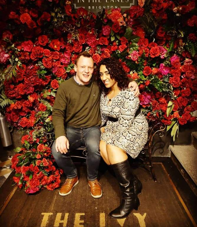 Couple sitting in front of a rose wall with The Ivy Brighton written on the sign.