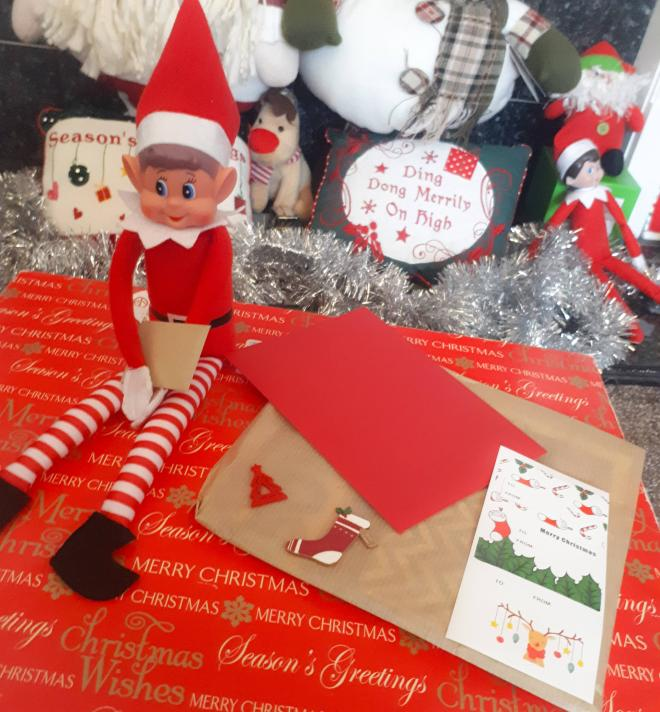 Elf sitting on a christmas box with a mini card in his hand next to stationery card and decorations.