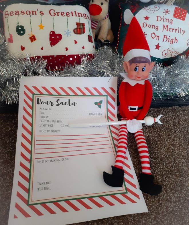 Toy elf next to a letter to Santa template. He's holding a pen