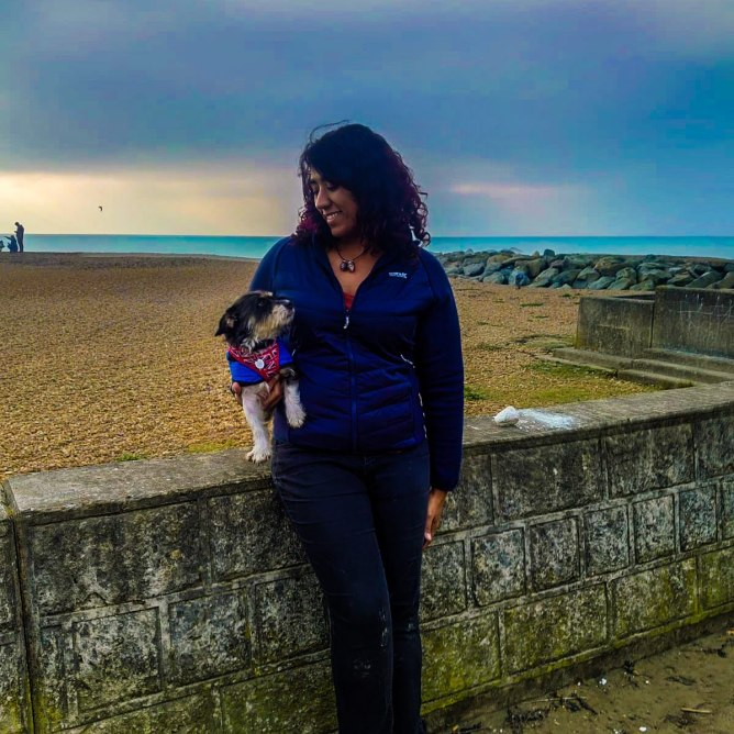 Woman leaning by a wall in front of the beach, holding her small dog