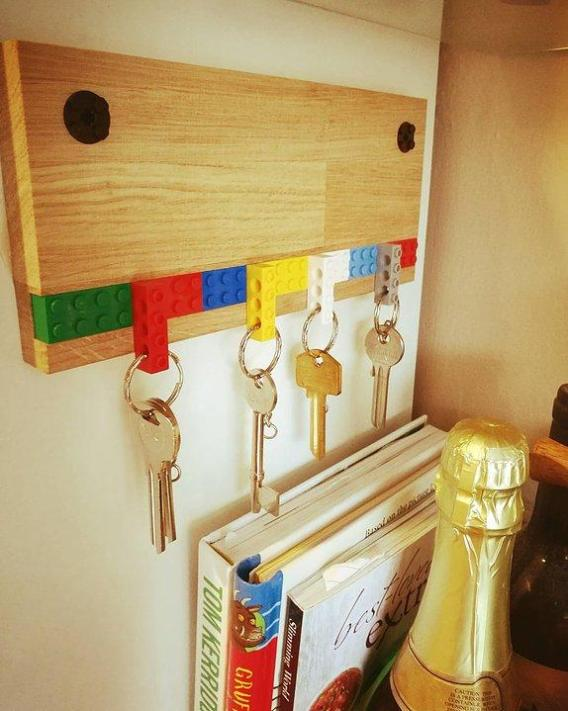 A wooden key holder mounted to a wall. There are Lego pieces attached that have 4 keys hanging from them.