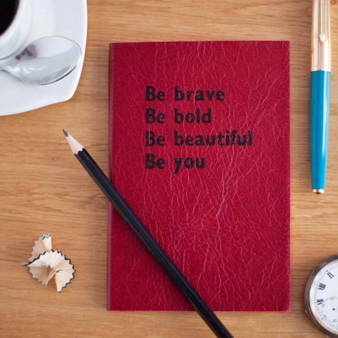 A red journal on a table, that says Be brave, Be bold, Be beautiful, Be you