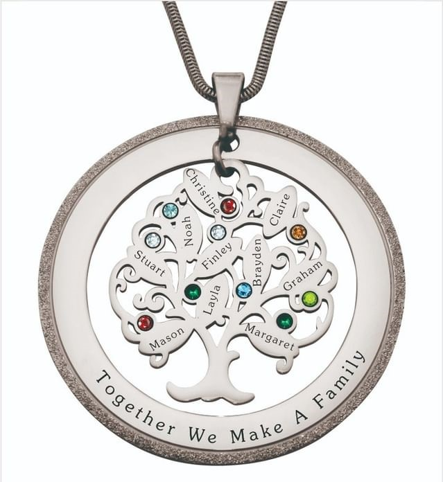 Close up of a silver pendant with a family tree on it. Each leaf has a name and birthstone on it.