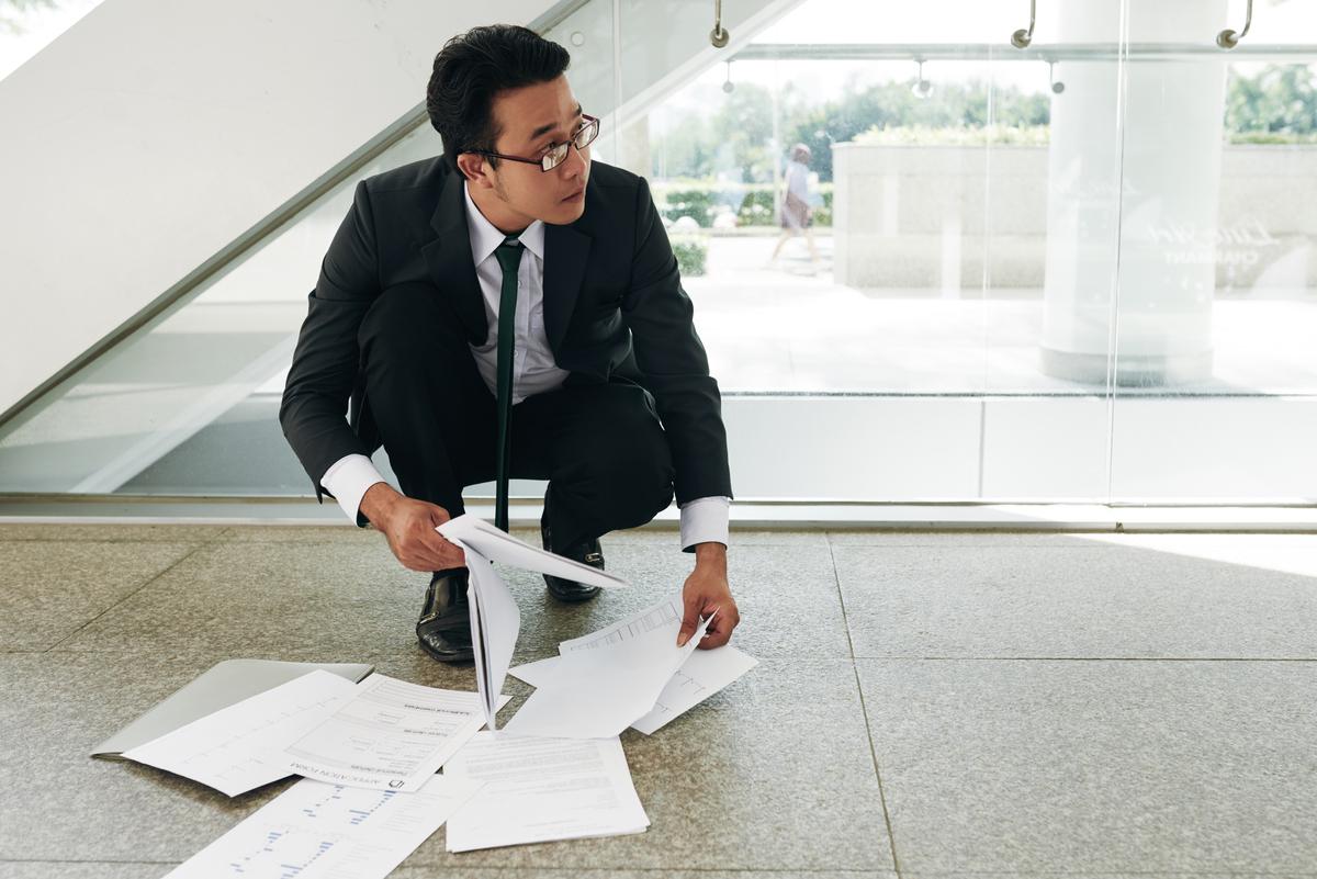 Executivo com documentos no chão