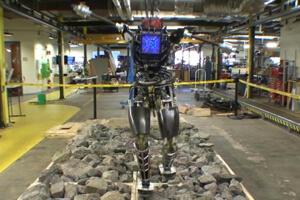 Boston Dynamics Atlas robot walking over a field of rubble.