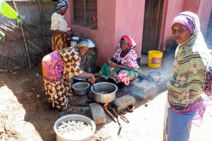 Women_cooking_using_the_open_fire_stove