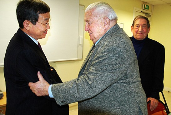 A Frenchman congratulates a DPRK representative for successfully launching a satellite.