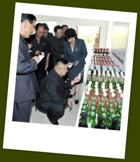 Doin' it for the folks at home. Kim squats to check out the local soju. | Image: KCNA