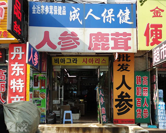 Traders pass a Chinese shop advertising Korean goods. | Image: Matthew Bates