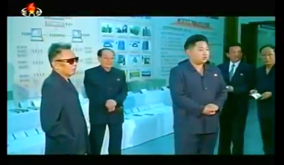 Kim Jong-un being uncharacteristically subdued at an early on-site inspection (probably 2009) with his father, left. Image via Chosun Central Television.