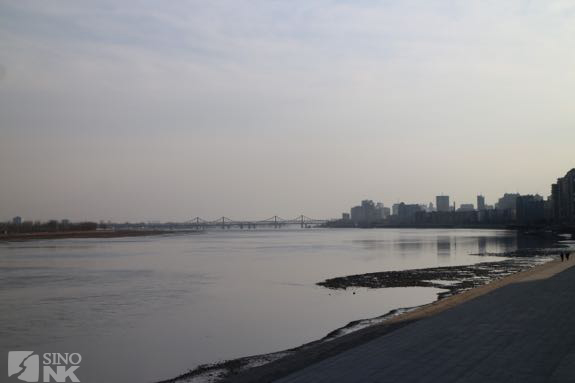 "Dandong (R), a place of ""last hope and the future"" just across the Yalu River from that elusive target, the DPRK and one of its border cities, Sinuiju (L). 