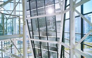 Glass structure with solar panels. The sun is glaring through the glass.