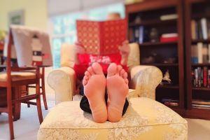 plante des pieds d'une personne en train de lire dans un fauteuil
