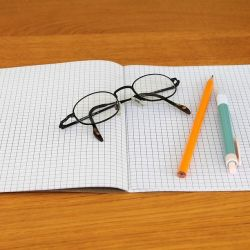 cahier ouvert, avec lunettes, crayon et stylo, prêt pour une leçon de grammaire!