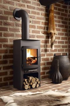 A modern designed stove in a traditional brick fireplace