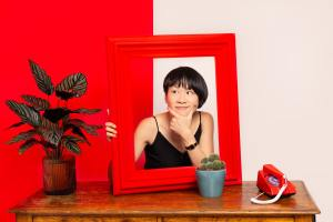 An asian woman in a black vest holds up a red frame on a wooden table with plants. Photograph by Siorna Ashby, a portrait photographer in north London, Finsbury Park.