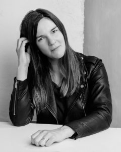 A woman smiling in a leather jacket on a London portrait photoshoot in black and white