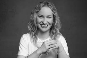 Female London headshot photo seated relaxed and smiling in black and white