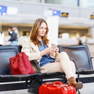 Young woman at international airport sitting waiting