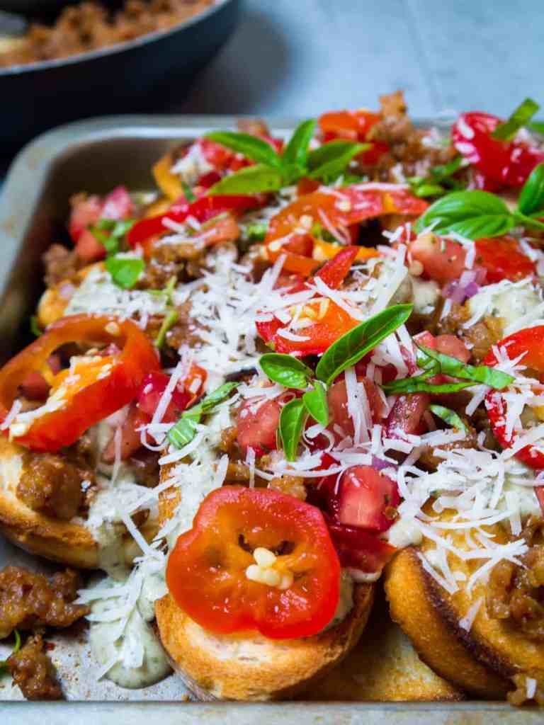 Take game day to another level with these delicious Italian Nachos with Spicy Sausage and Pesto Alfredo. They're everything you love about nachos, but they'd make any Nonna proud! Toasted bread is topped with spicy Italian sausage, tomato and cherry pepper relish and pesto alfredo! Make a big pan and watch them disappear!   Sip and Spice #gameday #nachos #Italian #pestoalfredo #snacks #dinner