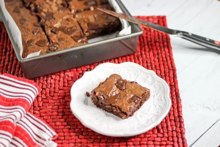 Metal sheet pan with chewy fudge brownies from scratch with one brownie on a white plate