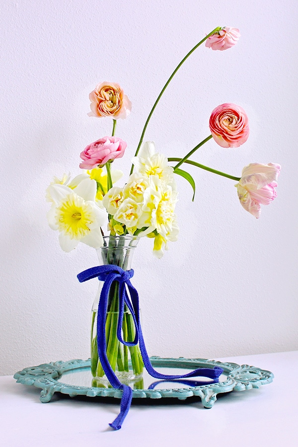 Learn how to prevent a simple floral arrangement from looking cheap in this tutorial for a floral arrangement with pink peonies on a mirror centerpiece.