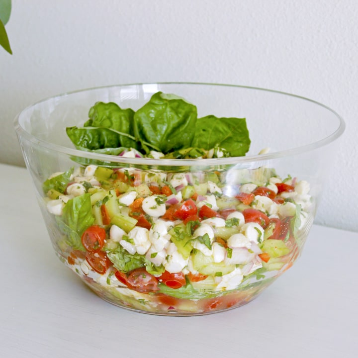white buffet table at a party with a bowl of summer vegetables including cucumber tomato and basil in a salad