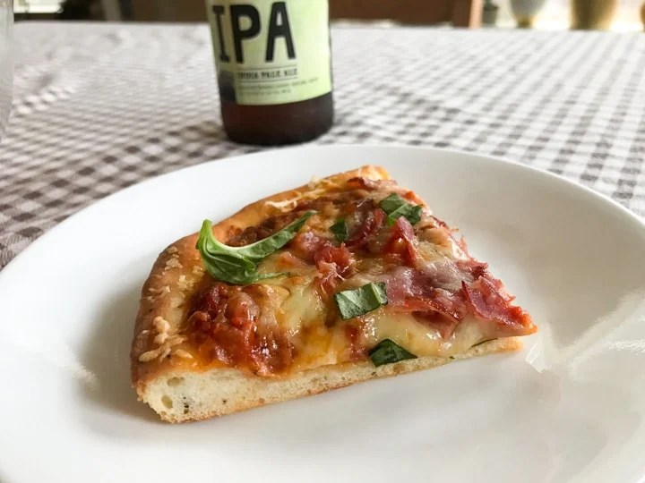 homemade pizza slice with ham cheese and basil on a plate with an IPA beer