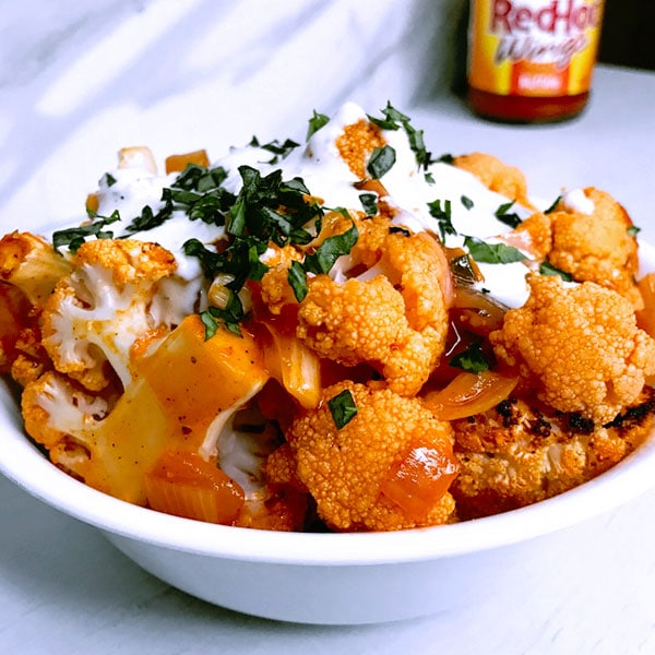 Easy baked buffalo cauliflower bites recipe with red onion with Franks Red Hot Sauce chicken wings alternative and Tobys dessing