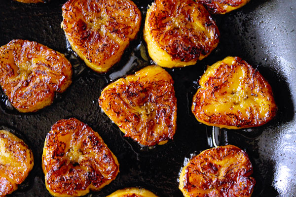 roasting fried sweet plantain slices in a pan