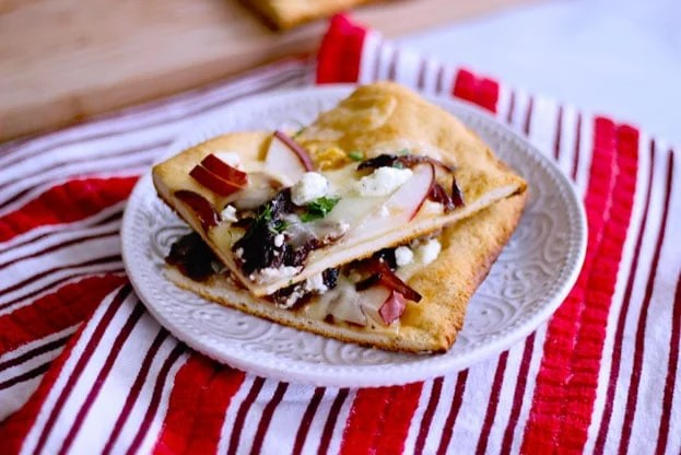 pear and goat cheese flatbread topped with caramelized onions, ham and cheddar