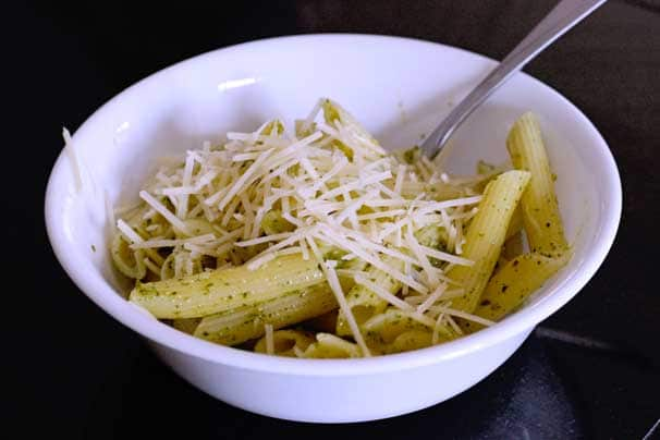 creamy pesto pasta in a salad bowl topped with Parmesan cheese