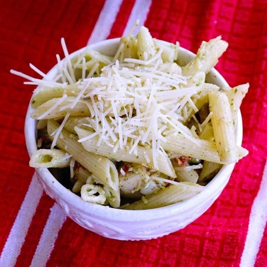 creamy pesto pasta salad in a white bowl on a red kitchen towel