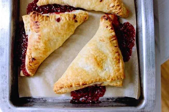 Fresh raspberry puff pastry turnovers baked in the oven on a sheet pan-5