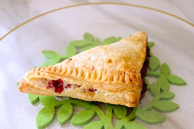 Fresh raspberry puff pastry turnovers on a glass plate for breakfast or dessert-4