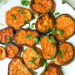 savory roasted sweet potatoes with blue cheese crumbles on a white plate